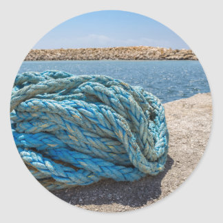 Coiled blue mooring rope at water in greek cave classic round sticker
