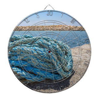 Coiled blue mooring rope at water in greek cave dartboard