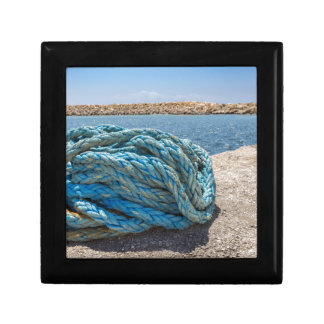 Coiled blue mooring rope at water in greek cave gift box