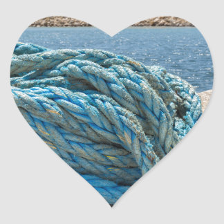 Coiled blue mooring rope at water in greek cave heart sticker
