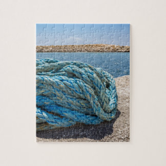 Coiled blue mooring rope at water in greek cave jigsaw puzzle