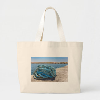 Coiled blue mooring rope at water in greek cave large tote bag