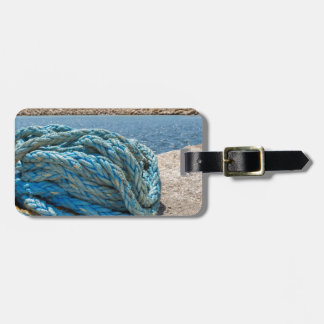 Coiled blue mooring rope at water in greek cave luggage tag