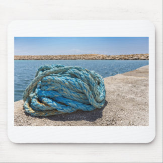 Coiled blue mooring rope at water in greek cave mouse pad