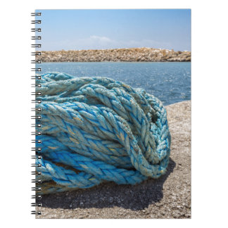 Coiled blue mooring rope at water in greek cave notebooks