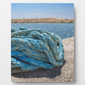 Coiled blue mooring rope at water in greek cave plaque