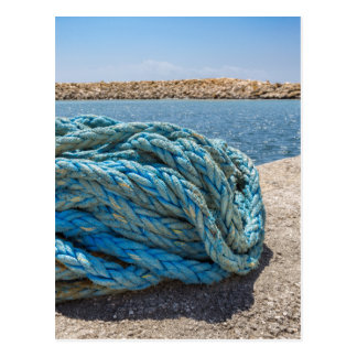 Coiled blue mooring rope at water in greek cave postcard