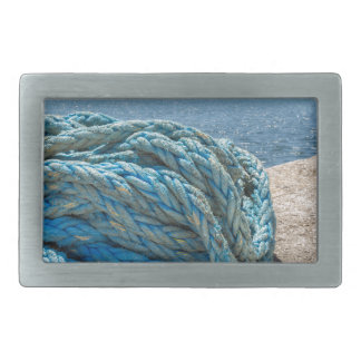 Coiled blue mooring rope at water in greek cave rectangular belt buckle