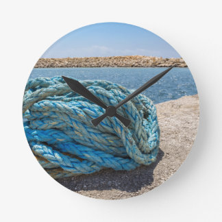 Coiled blue mooring rope at water in greek cave round clock
