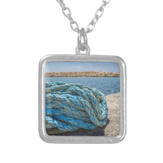 Coiled blue mooring rope at water in greek cave silver plated necklace