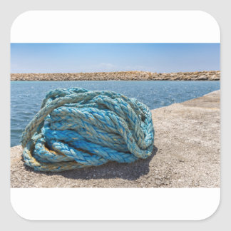 Coiled blue mooring rope at water in greek cave square sticker