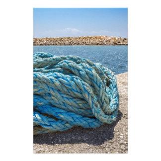 Coiled blue mooring rope at water in greek cave stationery