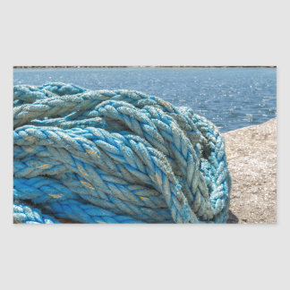 Coiled blue mooring rope at water in greek cave sticker