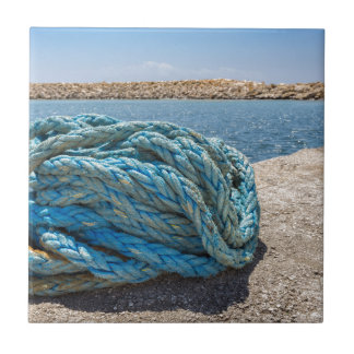 Coiled blue mooring rope at water in greek cave tile