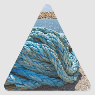 Coiled blue mooring rope at water in greek cave triangle sticker