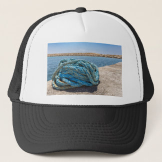 Coiled blue mooring rope at water in greek cave trucker hat