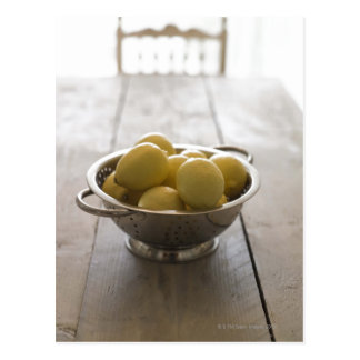Colander with lemons on wooden table postcard