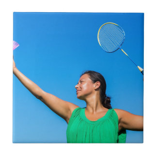 Colombian woman serve with badminton racket tiles
