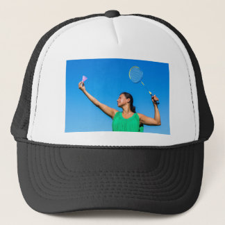 Colombian woman serve with badminton racket trucker hat