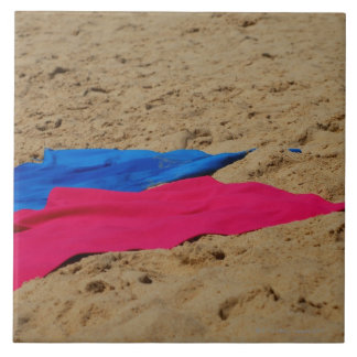 Colored towels on sandy beach tiles