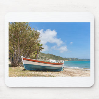 Colorful boat lying on greek beach mouse pad
