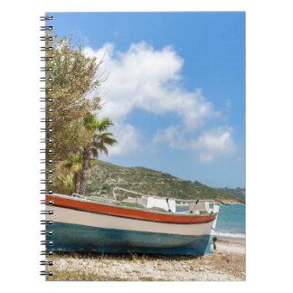 Colorful boat lying on greek beach notebooks