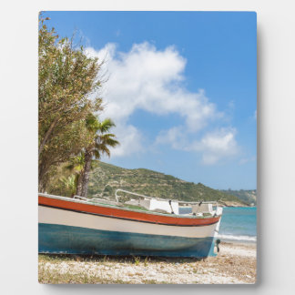 Colorful boat lying on greek beach plaque