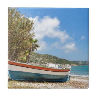 Colorful boat lying on greek beach tile