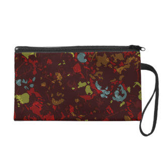 Colorful leaves and flowers against camouflage wristlet clutches