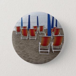 Colorful wooden chairs at sand beach 2 inch round button