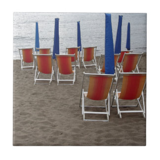 Colorful wooden chairs at sand beach tile