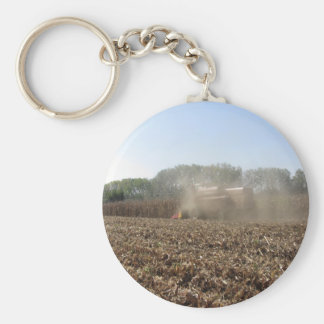 Combine harvesting corn crop in cultivated field keychain