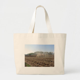 Combine harvesting corn crop in cultivated field large tote bag