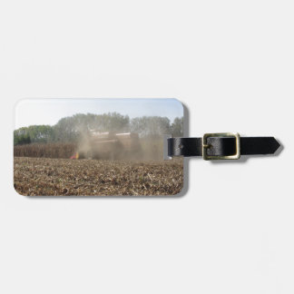 Combine harvesting corn crop in cultivated field luggage tag