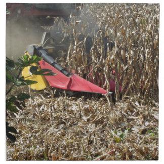 Combine harvesting corn crop in cultivated field napkin