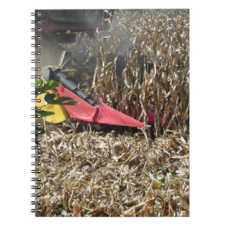 Combine harvesting corn crop in cultivated field notebook