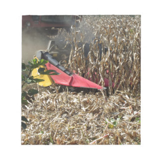 Combine harvesting corn crop in cultivated field notepad