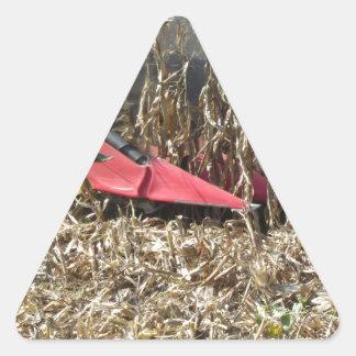 Combine harvesting corn crop in cultivated field triangle sticker