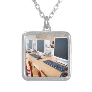 Computers in classroom on high school silver plated necklace