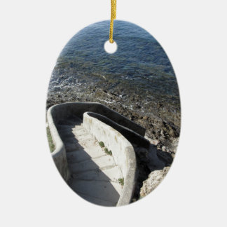 Concrete staircase down to the sea . Spiral stairs Ceramic Ornament