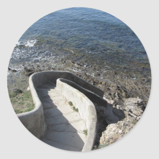 Concrete staircase down to the sea . Spiral stairs Classic Round Sticker