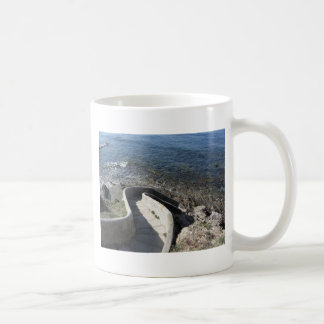 Concrete staircase down to the sea . Spiral stairs Coffee Mug