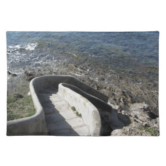 Concrete staircase down to the sea . Spiral stairs Placemat