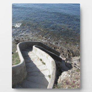 Concrete staircase down to the sea . Spiral stairs Plaque
