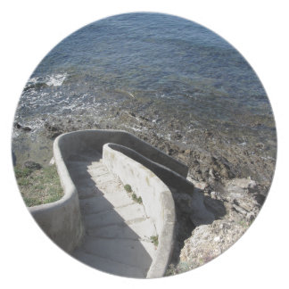 Concrete staircase down to the sea . Spiral stairs Plate
