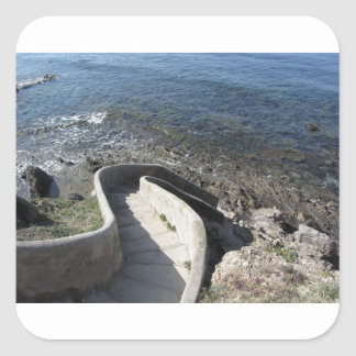 Concrete staircase down to the sea . Spiral stairs Square Sticker
