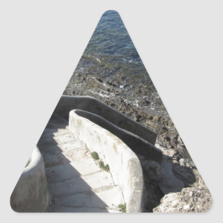 Concrete staircase down to the sea . Spiral stairs Triangle Sticker