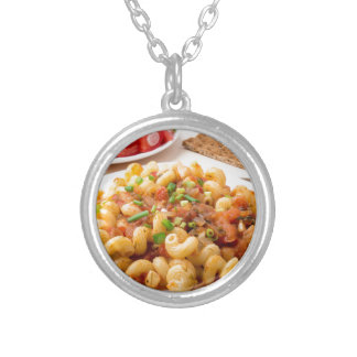 Cooked pasta cavatappi with stewed vegetable sauce silver plated necklace