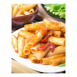 Cooked rigatoni pasta, seasoned with pepper letterhead