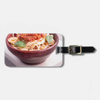 Cooked spaghetti in a brown small wooden bowl luggage tag